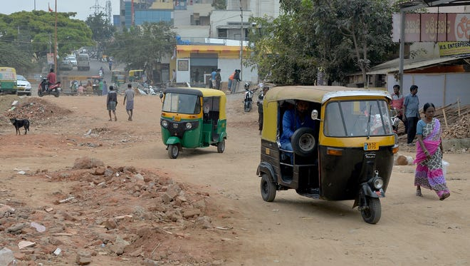 This photograph taken on November 1, 2017 shows rickshaws negotiating their way along a bumpy, unasphalted stretch of road in Bangalore.