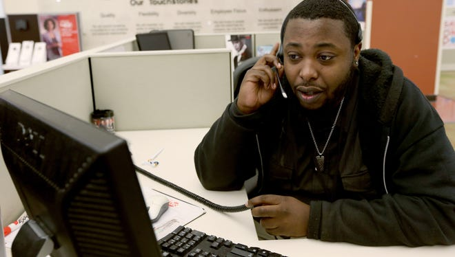 A customer associate speaks with a customer on the phone at a Comcast cable call center in Miramar, Florida.