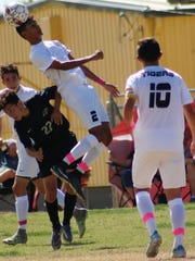 Alamogordo's Herbey Bustamante tries to win possession on a header.
