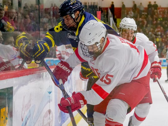 Sophomore forward Trevor Yates tried to gather the puck along the boards during the first period of Cornell's 5-2 win over Merrimack College on Jan. 9, 2016, at Lynah Rink.