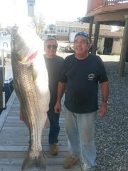 Rich Kimball (center) caught this 45-pound, 3-ounce striper on Wednesday off Casino Pier aboard Pete Hartman's (right) Mightygood. Both anglers are from Toms River.