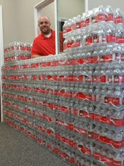 Kyle Libby is shown with some of the water that has been donated to various clubs and fundraising activities. He and his employees participate in what they call Pay it Forward Friday, and they are making a difference in the community 52 weeks of the year.