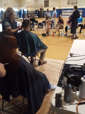 Stylist Danyel LaRue with Shear Attractions shapes up a man's hair at the first ever Haircuts for the Hopeful held last Sunday at Henderson Salvation Army.