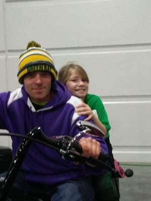 Peter Hann is clowning around with Alina Moran, the daughter of a friend, at a sports show. Neither rides a motorcycle.