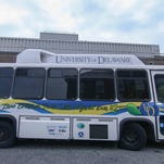 Ajay Prasad, director of the University of Delaware's Center for Fuel Cell Research (left), and Babatunde Ogunnaike, professor of UD's college of engineering, stand in front of a university bus they used to study the feasibility of a hybrid renewable energy system.