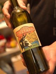Timmy Martinez displays a bottle of Rio Suave Vineyards wine Wednesday at his home in Blanco.