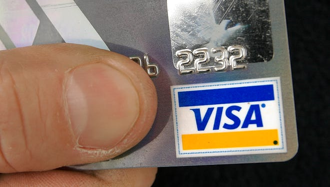 A cardholder poses with his Visa credit card