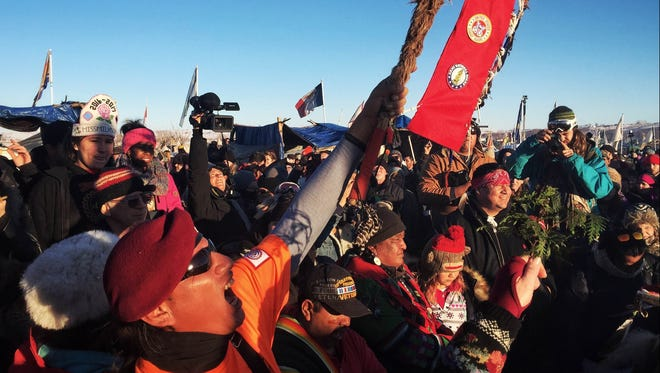 People celebrate around the sacred fire at the Oceti Sakowin Camp near Cannon Ball, N.D., on Sunday, Dec. 4, 2016. On Sunday afternoon, the Army Corps of Engineers announced it was halting construction on the Dakota Access Pipeline and considering alternate routes, something protesters had sought for months.