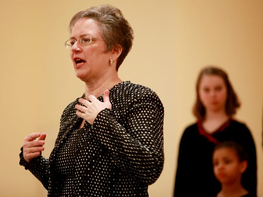 Director Julia White leads the girls in the Virginia Girlchoir in a rehearsal before their inaugural performance on Saturday, Dec. 6, 2014 at Tinkling Spring Presbyterian Church.