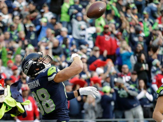Seattle Seahawks tight end Jimmy Graham tosses the football after scoring a touchdown in the second half against the Houston Texans during an NFL football game, Sunday, Oct. 29, 2017, in Seattle. (AP Photo/Elaine Thompson)