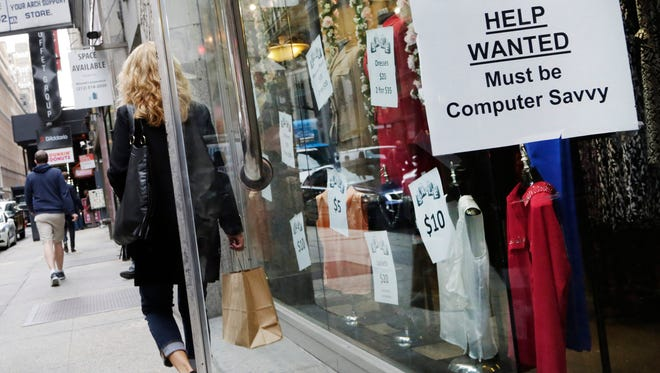 """In this Oct. 1, 2015 photo, a shopper walks past a store with a """"Help Wanted"""" sign in the window, in New York.  The Labor Department said Friday, that jobless rates fell in 27 states, rose in 11, and were unchanged in 12 states. Employers added jobs in 35 states, while employment fell in 14."""