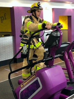 Berlin Firefighter Jon Gallardo on Sept. 11, tacking 110 floors on a StairMaster. He was dressed in full turnout gear, weighing about 60 pounds.