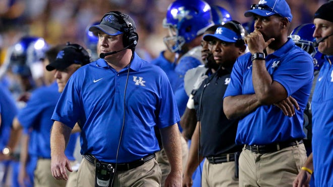Kentucky head coach Mark Stoops walks the sideline with his coaching staff in the first half of an NCAA college football game in Baton Rouge, La., Saturday, Oct. 18, 2014. LSU won 41-3.  (AP Photo/Gerald Herbert)