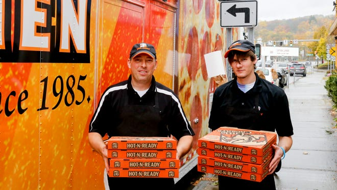 Little Caesar's franchise owner Bill Beveridge, left, and employee Josh Gates carry pizzas into the Rescue Mission on Wednesday afternoon.