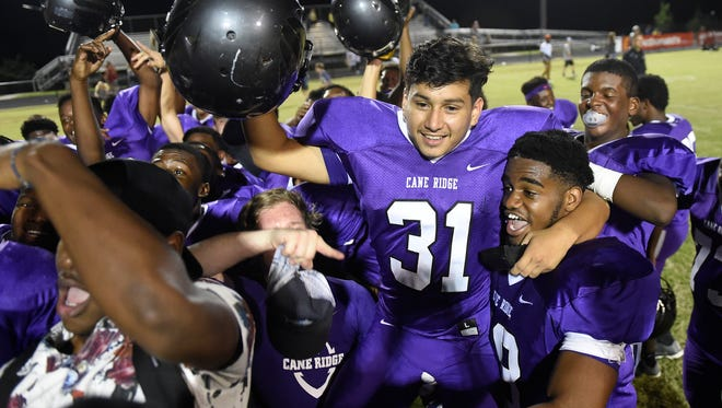 Cane Ridge kicker Carlos Velasquez, 31, is lifted onto the shoulders of his teammates after he kicked the game winner to top Hendersonville 47-46 in overtime on Friday, September 2,  2016.