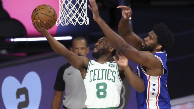 Boston Celtics guard Kemba Walker (8) shoots past Philadelphia 76ers center Joel Embiid, right, during the first quarter of Game 4 of their first-round playoff series, Sunday, Aug. 23, 2020, in Lake Buena Vista, Fla.