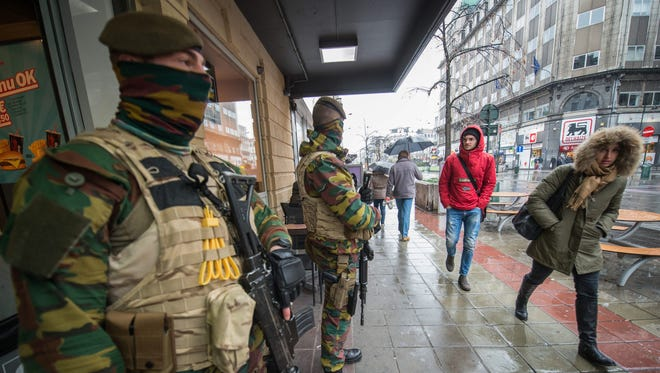 Armed military men stand guard in front of a restaurant in downtown Brussels.