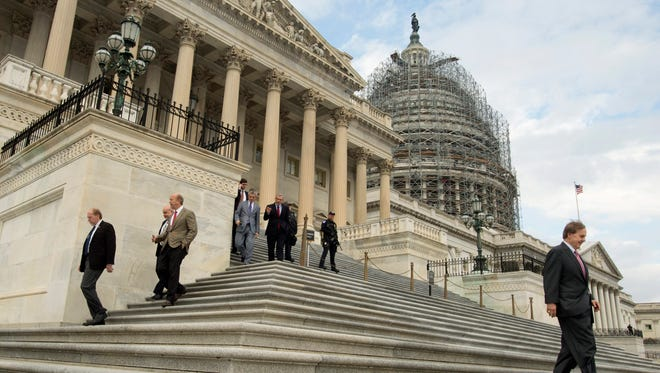 Members of Congress and aides walk down the East Front steps of the US House of Representatives following the last scheduled vote of the year, on Capitol Hill Friday.