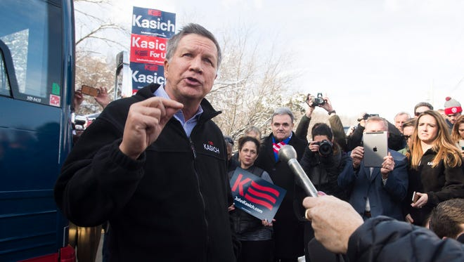 Republican presidential candidate John Kasich (L) speaks to campaign volunteers and members of the news media in Manchester, New Hampshire Saturday.