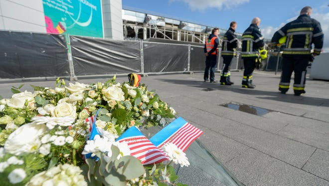 A floral tribute (L) to the victims is placed by U.S. Secretary of State John Kerry (unseen) during Kerry's visit to the Brussels National Airport.