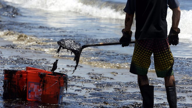 A volunteer worker shovels sludge on an oil contaminated beach after an underwater oil pipe ruptured spilling an estimated 21,000 gallons of oil into the Pacific Ocean near California?s Refugio State Beach.