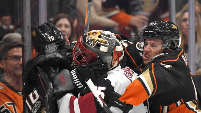 Oct 5, 2017; Anaheim, CA, USA; Arizona Coyotes goalie Louis Domingue (35) (center) fights with Anaheim Ducks right wing Corey Perry (10) (left) and center Rickard Rakell (67) in the second period during a NHL hockey game at Honda Center. Mandatory Credit: Kirby Lee-USA TODAY Sports