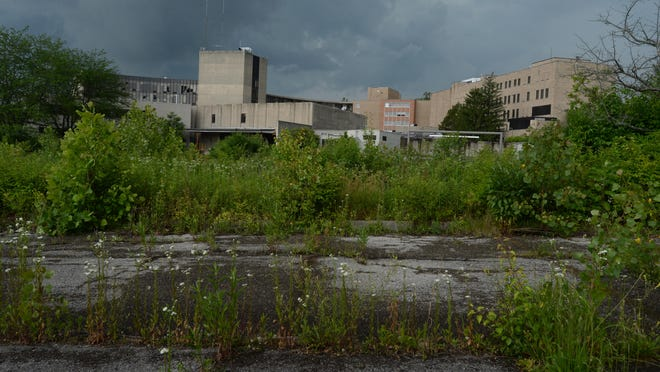 Grass and weeds grow up through concrete at the former Reid Hospital site in Richmond.
