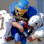 Central Catholic's Nolan Donisthorpe is tackled by Belt's Matt Metrione, left, and Tristan Cummings, right, Saturday at Central Catholic High School.