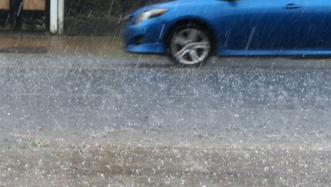 Hail and heavy rain fall on Third Street in Monroe on Thursday.