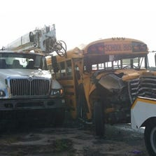 A school bus and a utility vehicle sit damaged after a collision on Sept. 18, 2014.