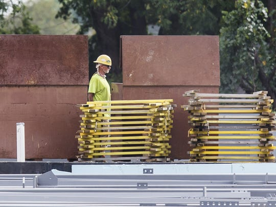 A worker walks through the construction site of the new library being built off of Del. 9 near New Castle last month.