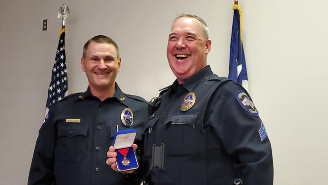 Brownwood police Sgt. Art Shannon holds his lifesaving award as he stands next to Police Chief Ed Kading.