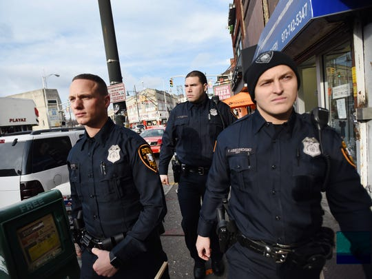 Three Paterson Police Officers, (L to R) Edward J. Akins, Salvador Brancato and Ferdi Abedinoski who graduated from Police Academy last week, walk the streets during their patrols for the first time in commercial shopping districts in downtown Paterson on 12/19/17.