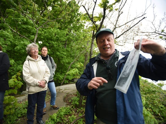 Historical interpreter Eric Nelsen explains about an historical photo as participants including Maureen Graham (2nd from L) of Cresskill listen as he leads an annual tradition of a special Mother's Day Hike along the summit of the Palisades Interstate Park in Alpine on 05/13/18.