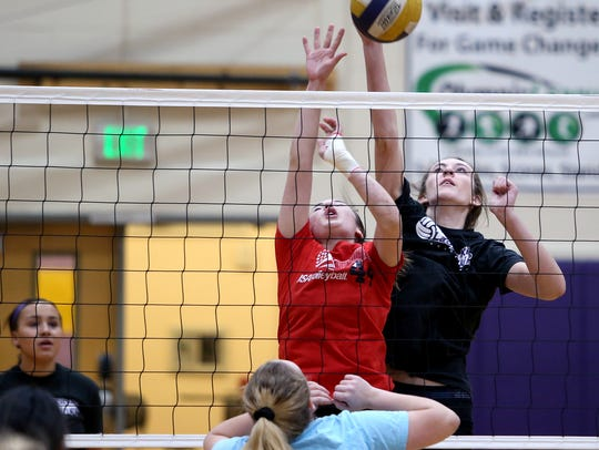 North Kitsap volleyball players Autumn Carver, center, and Taylor Clodfelder team up for a block during a recent practice. The NK coaches emphasize constant competition in practice.