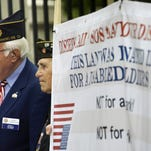 In this 2011 file photo, veterans, including John L. Stamatiades, left, hold a banner at a news conference to announce a lawsuit against the federal government, at the Los Angeles Veterans Administration center in Los Angeles.