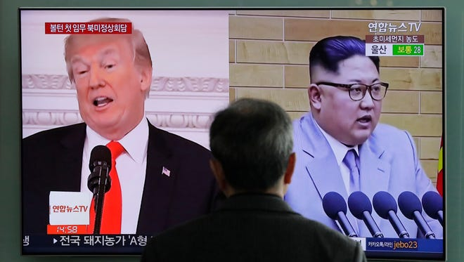 A man watches a TV screen showing file footages of U.S. President Donald Trump, left, and North Korean leader Kim Jong Un, right, during a news program in Seoul, South Korea.
