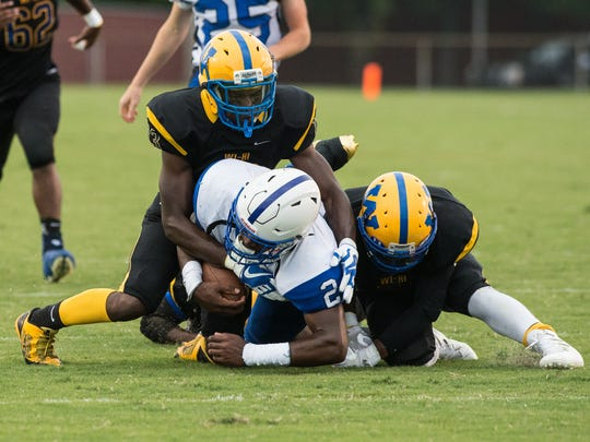 Wi-Hi players tackle North Caroline's David Bailey (2) during a game at Wicomico County Stadium on Friday, Sept. 1, 2017.
