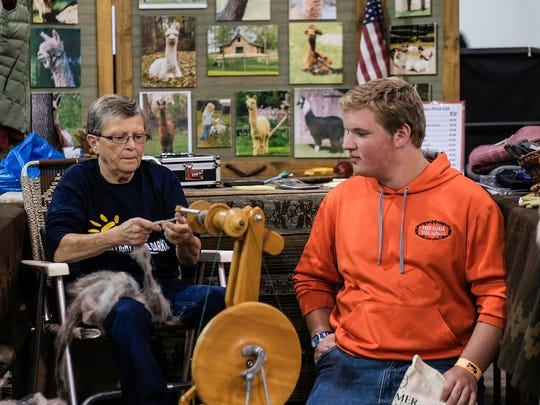 Linda Bader from Bad Axe, shows Alan Fisher, 16,  from Dryden her spinning techniques at the Alpaca Fest held at the Summit in Dimondale Saturday, October 1, 2016.