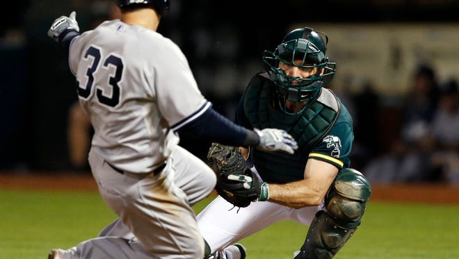 The Yankees' Kelly Johnson is tagged out at home plate by Oakland Athletics catcher John Jaso during the fifth inning at O.co Coliseum.