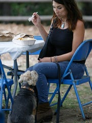 Tiffany Ghilglia enjoys a taco during the Ojai Valley Mexican Fiesta as her dog, Rocco, waits for his own taste of the food.