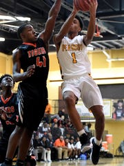 Peabody's Jadarius Harris attempts to make a shot over Middleton's Maurius Reaves during their game, Friday, December 8. Middleton defeated Peabody 68-61.