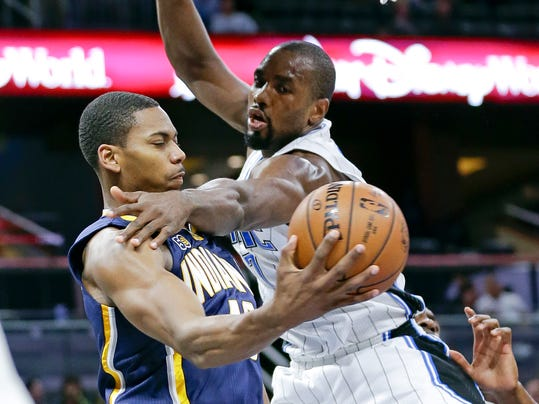 Indiana Pacers' Glenn Robinson III, left, passes the ball as Orlando Magic's Serge Ibaka defends during the first half of an NBA basketball game, Wednesday, Feb. 1, 2017, in Orlando, Fla. (AP Photo/John Raoux)