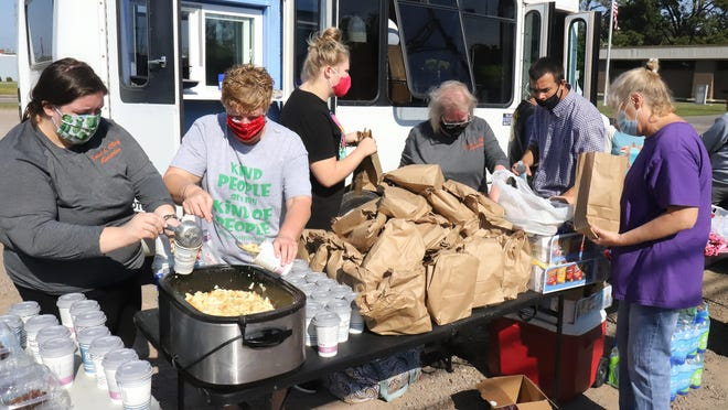 Volunteers from Trust and Obey Ministries join the staff of We Inc., Saturday, Oct. 9, at the corner of N 5th and B St. to feed the hungry in the area.