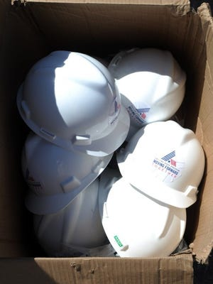 Nellie Doneva/Reporter-News Hard hats arrived in a box for the groundbreaking.