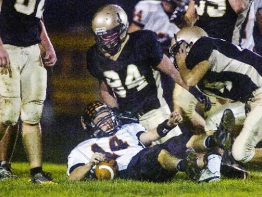 York Suburban quarterback Kris Reinhold gets up after being knocked to the ground by a group of Delone Catholic defenders