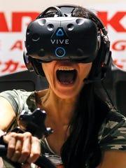 A gamer wearing Vive VR goggles at a virtual gaming