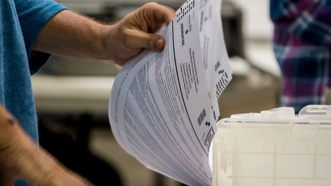 Staff members go through piles of absentee ballots at the Elections Service Center in Riviera Beach Thursday.
