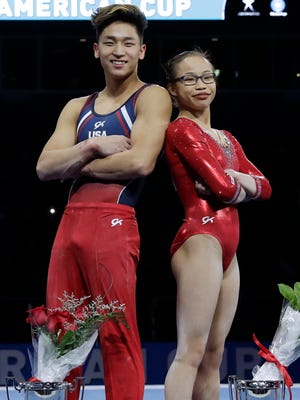 Yup Moldauer, left, and Morgan Hurd pose with the victor's trophies at the American Cup gymnastics competition Saturday in Chicago.