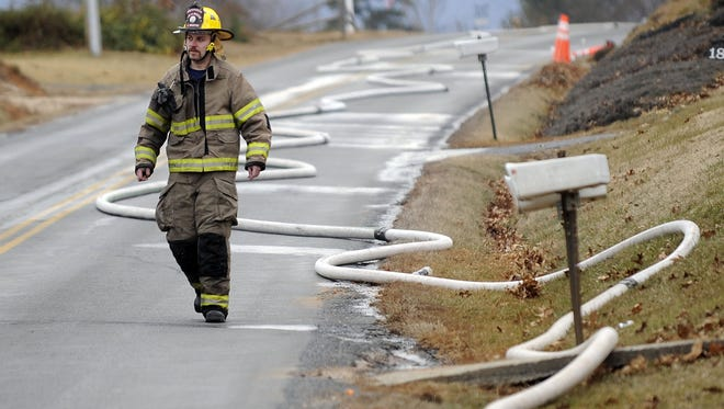 This January 2011 file photo shows a firefighter walking past a hose winding down Howardsville Turnpike in Sherando while firefighters battled the blaze house fire.